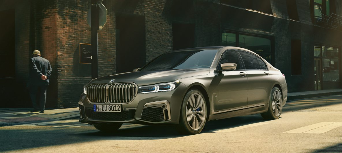 BMW M760Li xDrive Limousine, seitliche Frontaufnahme fährt auf Straße in urbaner Kulisse