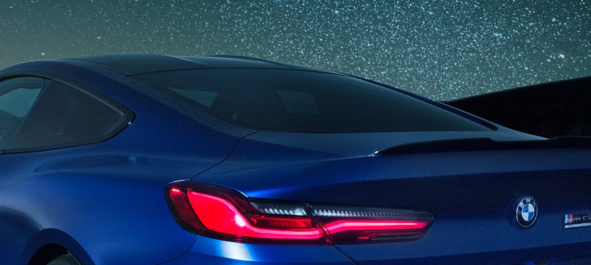 BMW M8 Competition Coupé in Marina Bay Blau metallic, nächtliche Nahaufnahme Schulterpartie mit M Heckspoiler aus Carbon.